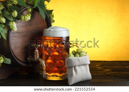 Beer barrel with fresh hop cones and glass of beer on table still life