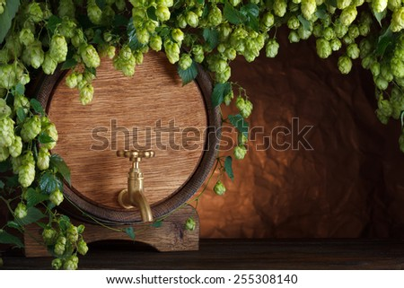 Beer barrel with fresh hops on wooden table still-life - stock photo