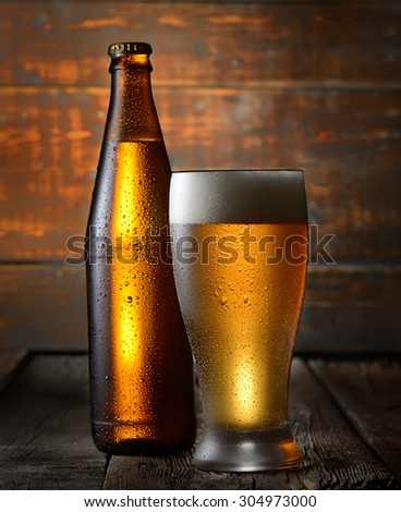 Beer. Beer bottle and glass on a wooden background - stock photo