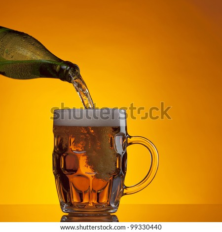 Beer being poured into a glass mug on gold/orange background.