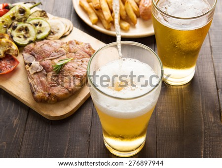 Beer being poured into glass with gourmet steak and french fries on wooden background - stock photo