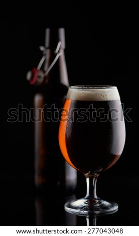 beer bottle and a cup on a black background - stock photo