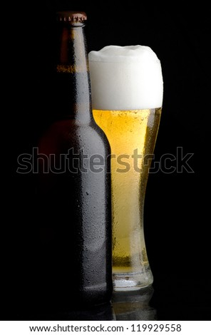 Beer bottle and glass of cold beer on black background