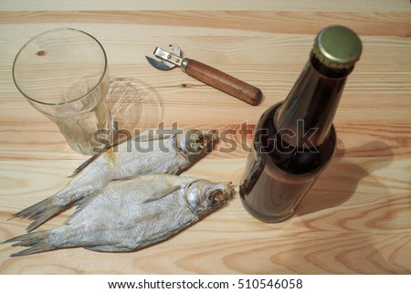 Beer bottle on a wooden table. Russian snack . Beer and dried fish. Light beer and smoked fish on the table. Peanuts, dried fish and beer.