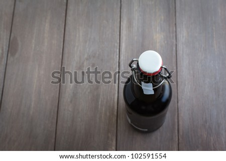 Beer bottle on brown planks. - stock photo