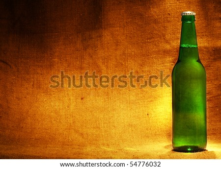 beer bottle on sacking with copy-space - stock photo