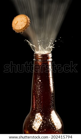 Beer bottle popping its top. - stock photo
