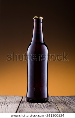 Beer bottle with without drops on a wooden table
