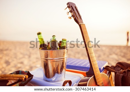 Beer bottles in a bucket of ice in the sand on a tropical beach. Guitar,backpack and everything is ready for party. Depth of field, selective focus - stock photo