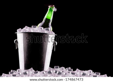 Beer bottles in ice bucket isolated on black