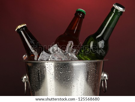 Beer bottles in ice bucket on darck red background - stock photo