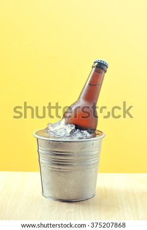 Beer bottles in ice bucket on wood table