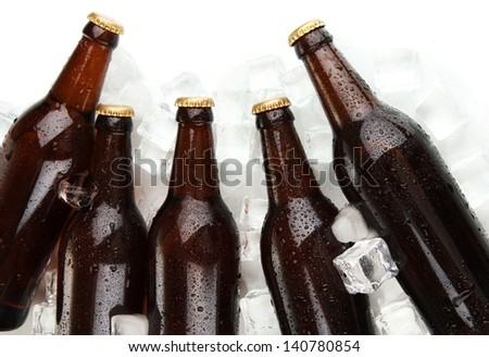 Beer bottles in ice cubes close up - stock photo