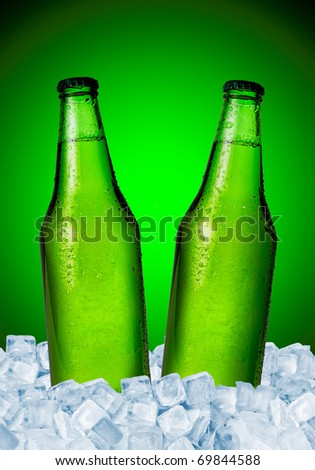Beer bottles in ice over green background - stock photo