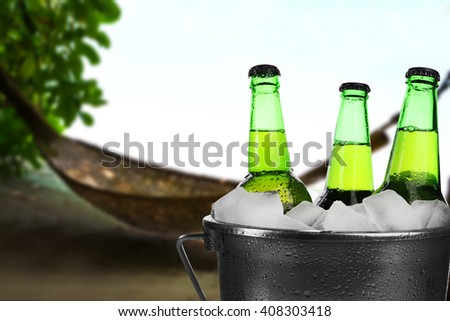 Beer bottles of cold fresh beer in ice bucket, on nature background - stock photo
