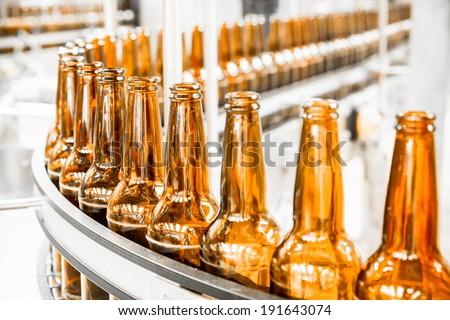 Beer bottles on the conveyor belt - stock photo