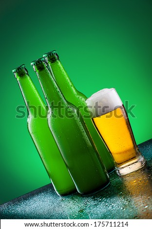 Beer bottles with glass against vivid background - stock photo