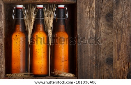 Beer bottles with wheat stems in old wooden crate still life, with copy space - stock photo