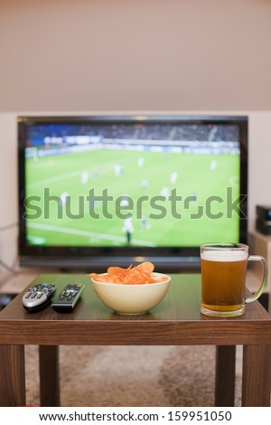 Beer, chips and remote controls on the table (in the background TV - football game) - stock photo