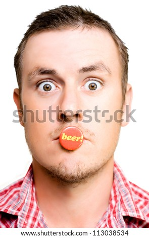 Beer crazy male dipsomaniac with a wild wide eyed stare and a button marked Beer clenched in his teeth as he wildly looks around for his next drink to satisfy his insatiable appetite for beer - stock photo