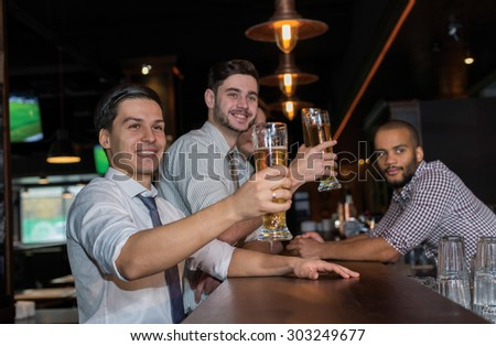 Beer evening in a pub. Male friends are drinking beer in a pub after working day. Beer glasses.  Beer pub concept. Men are waiting for football and beer