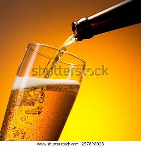 beer flows in to a glass with dew drops - stock photo
