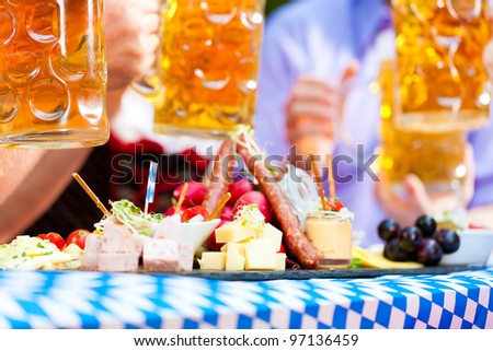 Beer garden restaurant in Bavaria, Germany - beer and snacks are served, focus on meal - stock photo