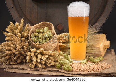 beer glass and beer barrel with hops, wheat, grain, barley and malt - stock photo