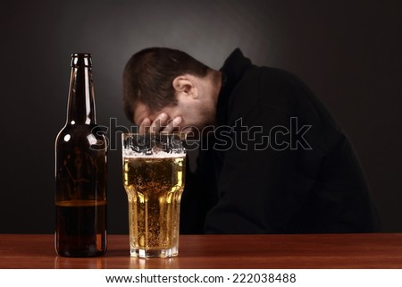 beer glass and bottle, alcoholic in despair, drunk man - stock photo
