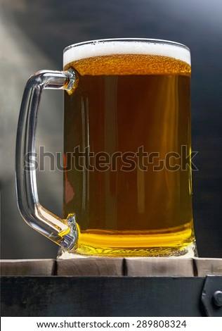beer glass of beer on a wooden barrel