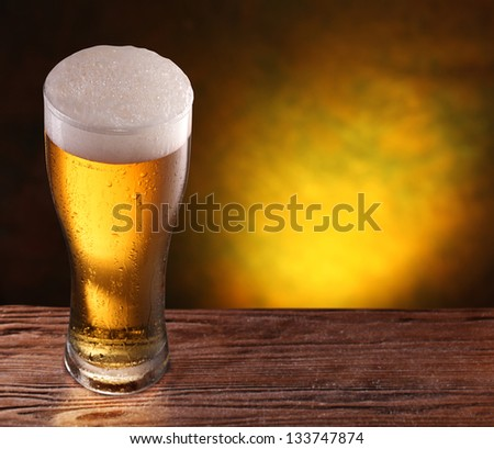 Beer glass on a wooden table. Copyspace. Dark yellow background. - stock photo