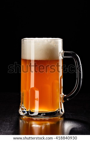 Beer Glass on black. Bar drink. Beer bubbles closeup. DRAFT LIGHT. Overflow beer glass. Beer beverage. Glass of alcohol. Closeup draft beer glass. Cold Beer. Pint of beer. Good for brewery commercial - stock photo