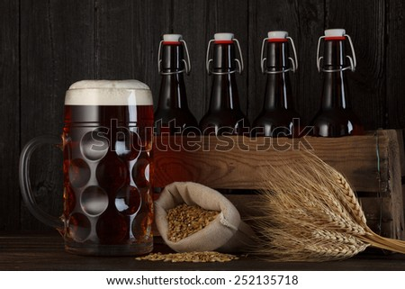 Beer glass on table with crate full of bottles, with brewing barley and wheat bunch, dark wooden background - stock photo