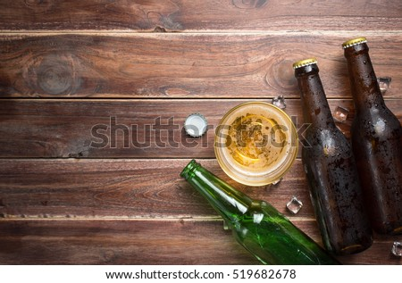 Beer glass with bottle cap and bottle on rustic wood background,space for text,top view