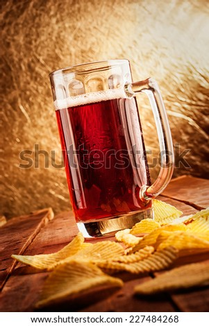 Beer glass with chips on the table