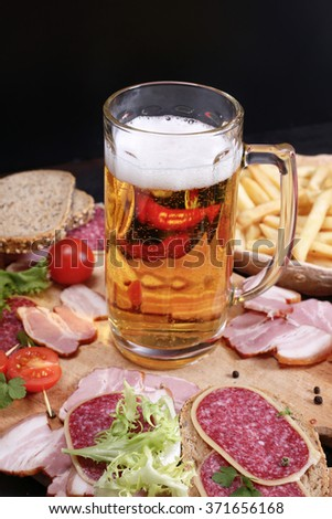 Beer glass with light beer with foam, meat on the board, lettuce and french fries, pub interior - stock photo