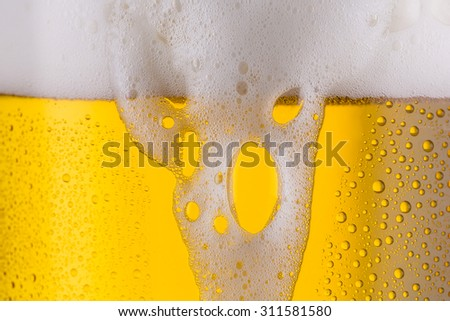 beer glass with overflowing beer froth an dew drops - stock photo