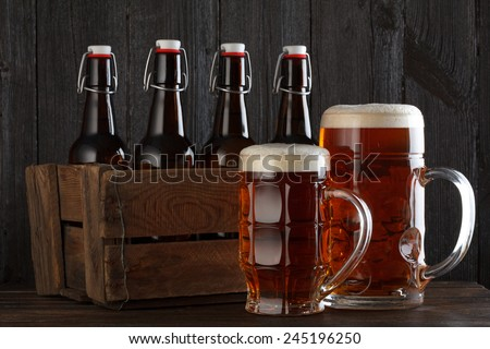 Beer glass with vintage wooden box full of beer bottles on wooden table still life - stock photo