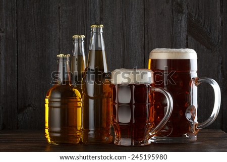 Beer glasses and bottles with variety of beer on wooden table still life - stock photo