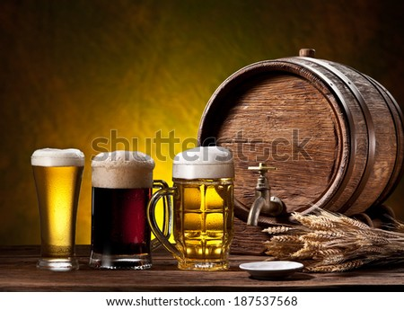 Beer glasses, old oak barrel and wheat ears on wooden table. - stock photo