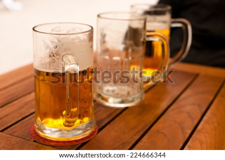 Beer glasses on a wooden table - stock photo