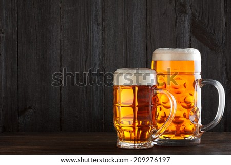 Beer glasses on table with burlap cloth, dark wooden background with copy space