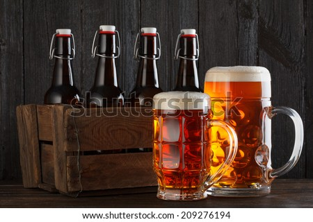 Beer glasses on table with crate, dark wooden background - stock photo