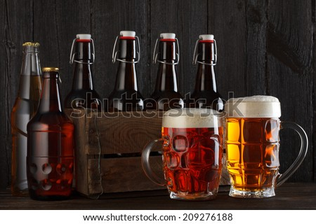 Beer glasses on table with crate full of bottles, dark wooden background - stock photo