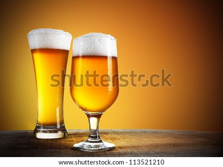 Beer glasses with gold background - stock photo