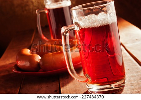 Beer glasses with  sausages on the table