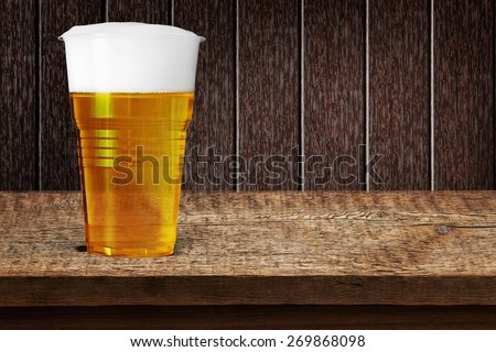 Beer. Golden beer, ale or lager in a plastic disposable cup or glass for party concert or by pool for safety - stock photo