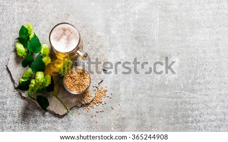 Beer, green hops and malt on a stone surface. Top view - stock photo