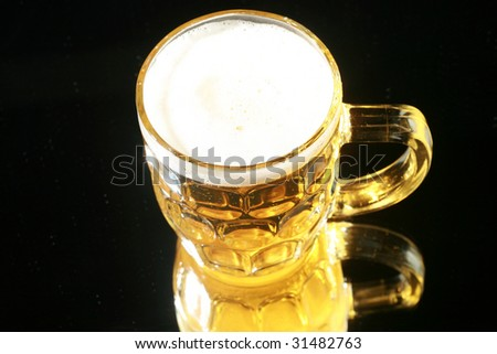 Beer in a Beer Mug on black with a mirror for reflections - stock photo