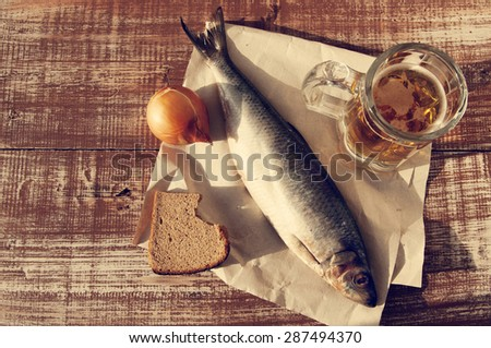 Beer in a glass, a salty herring on paper, bread and onions on a structural wooden table. Beer and snack to beer. - stock photo